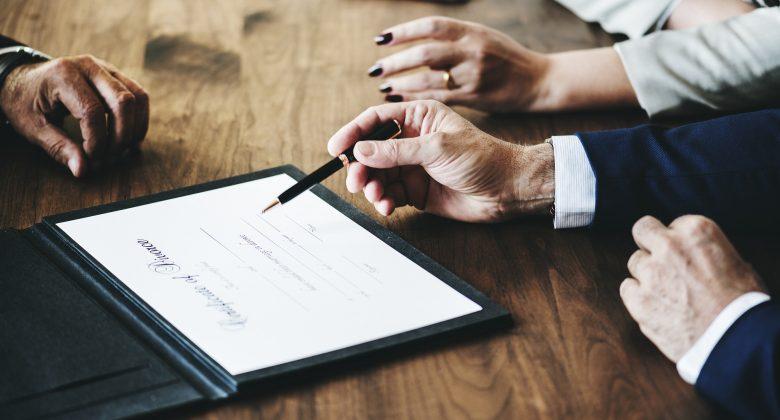 Imagem mostrando pessoas planejando ao redor de um tablet, o tablet mostra um texto jurídico