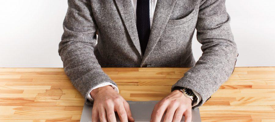 Homem de terno cinza digitando em um notebook