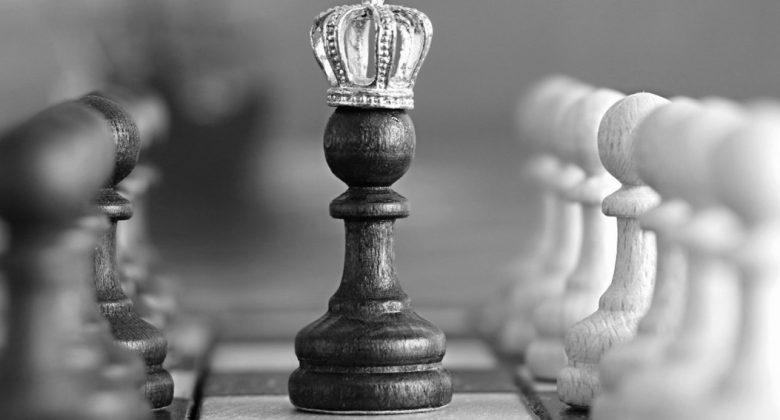 Peão de xadrez com coroa, no meio do tabuleiro, em destaque em relação aos demais