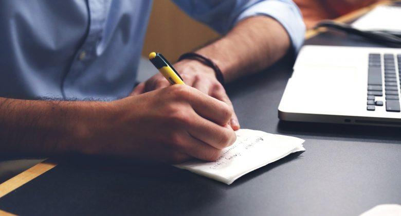 Pessoa fazendo anotações, enquanto trabalha no computador